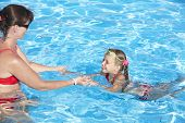 Chica de Instructor aprender niños nadar en la piscina.