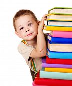 Little boy holding stack of books.