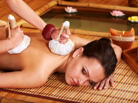 stock photo of thai massage  - Young woman getting massage in bamboo spa - JPG