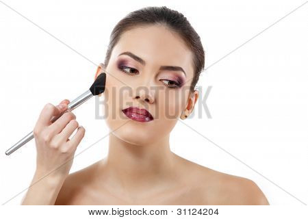 poster of beauty portrait of young beautiful woman with hand of esthetician applying rouge with brush isolated on white background