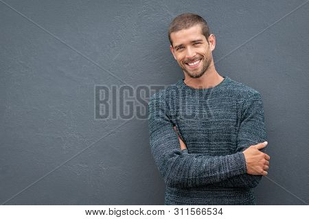 poster of Portrait of happy young man leaning against wall isolated on grey background with big smile. Cheerfu