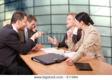 Picture or Photo of Business negotiations - 2 men 2 women sitting at the desk in the office