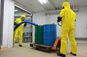 Two specialists in protective uniforms,masks,gloves and boots  working with barrels of toxic waste  in factory