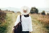 Hipster Girl With Backpack Traveling On Top Of Sunny Mountain And Looking At Hills And Woods. Stylis poster