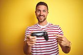 Young handsome man playing video games using joystick game pad over yellow background very happy poi poster