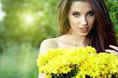 Young happy girl in yellow flowers, outdoor photo session