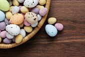 Still life photo of speckled candy covered chocolate easter eggs in a wicker basket on a rustic wood