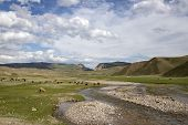 Sheep Grazing On The Banks Of The River Flowing Through The Pasture Against A Cloudy Sky With Mounta poster