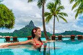 Luxury hotel vacation resort Asian woman tourist relaxing in swimming pool enjoying tropical getaway poster