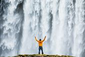 Man admirnig the beauty of iconic Skogafoss waterfall in Iceland, Europe. poster