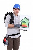 Fed-up tradesman pointing to an energy efficiency rating of G