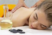 Spa Hot Stone Massage. Attractive Beautiful Girl Lying On Massage Bed In Spa Salon. Spa Aroma Therap poster