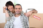 Couple moving into new home with doorkeys and boxes marked fragile