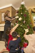 Hispanic family decorating Christmas tree