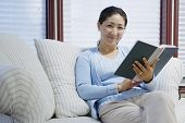 Retrato de mujer sentada en el sofá leyendo el libro