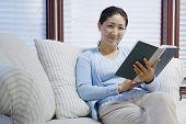 Portrait of woman sitting on loveseat reading book
