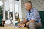 Profile of elderly man sitting at table typing on laptop