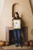 Hispanic teenage girl holding her own baby photograph