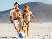 Summer beach couple playing with a beach ball on the sand, laughing and enjoying the sunshine outdoo