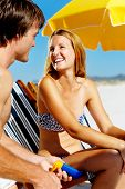 Summer beach couple take care of their skin with sunblock lotion of high SPF for maximum protection