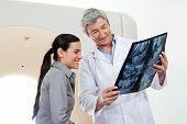 Mature male radiologist showing x-ray report to young female patient
