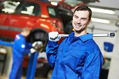 Young repairman auto mechanic inspecting car during automobile maintenance at engine auto repair sho