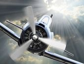 Dramatic scene on the sky. Vintage fighter plane inbound from sun. Retro technology background.