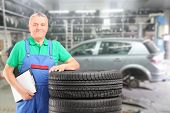 Mature auto mechanic posing on a tires in front of car during automobile maintenance at auto repair