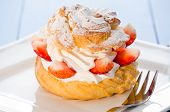 stock photo of cream puff  - fresh cream puff with whipped cream and strawberries on white plate and light blue wood table - JPG