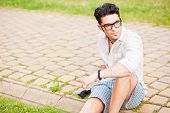 Handsome Man Wearing Glasses Sitting On The Sidewalk Looking Away