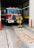 image of fire-station  - Young woman stands in front of firetruck at fire station - JPG