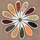 Pulses vegetable selection of peas, beans and lentils in white porcelain bowls over hessian background.