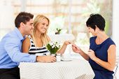 stock photo of fiance  - happy young woman with fiance showing her engagement ring to her mother - JPG