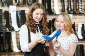 two Young woman choosing shoes during footwear shopping at shoe shop