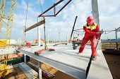 image of millwright  - builder worker in safety protective equipment installing concrete floor slab panel at building construction site - JPG