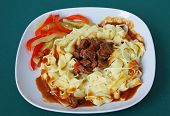 beef meat goulash with sauce,pasta and vegetable salad