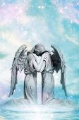 stock photo of archangel  - a statue of two angels with rays of light and stars - JPG