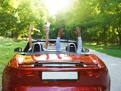 stock photo of hands-free  - Happy free couple driving in red retro car cheering joyful with arms raised - JPG