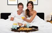 young couple enjoying a rich breakfast in bed with croissants, fresh orange juice, boiled eggs and tea on a tray on a bright Sunday morning