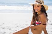 Cheerful young tanned woman wearing straw hat posing on the beach