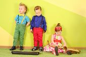 Mods three children at a bright green wall with trumpet, microphone and toy piano