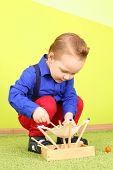 The boy mod in a blue shirt and red jeans squatting and playing with wooden toy