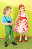 Mod girl and boy in bright clothes on a background of yellow green wall