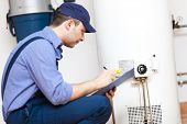 stock photo of plumber  - Plumber repairing an hot - JPG