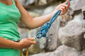 Female rock climber adjusting harness by the rock face