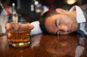 Drunk businessman with whiskey in his hand lying on a counter in a classy bar