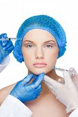 Surgeons making injection on content blonde wearing blue surgical cap on white background