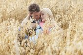 Romantic young couple relaxing amidst field