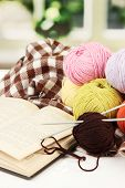 Multicolored clews with book and plaid closeup