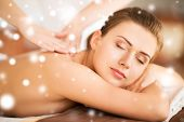 health and beauty concept - beautiful woman in spa salon getting massage